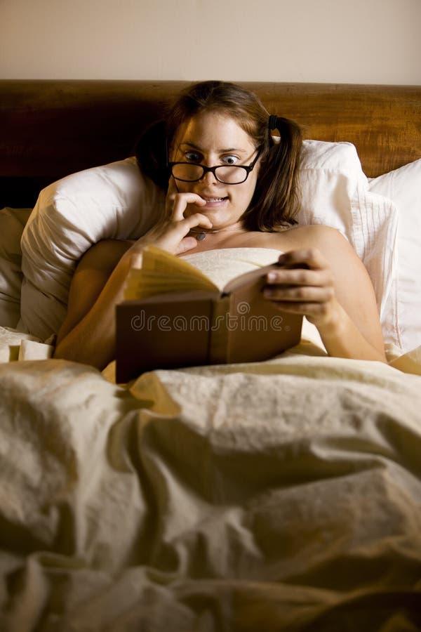 Lectura de la mujer en cama foto de archivo