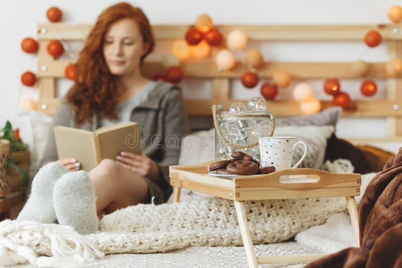 Lectura de la mujer en cama imagen de archivo