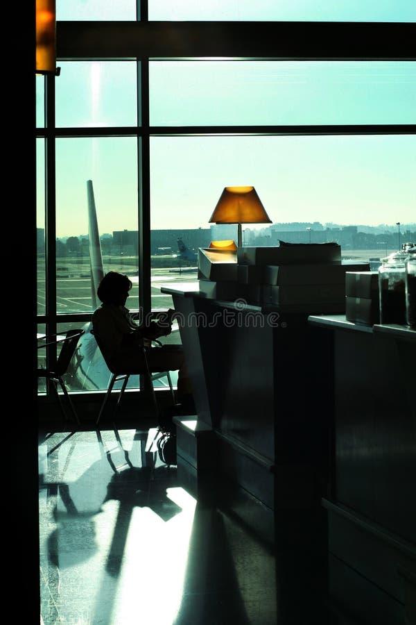Lectura de la mujer en el aeropuerto fotos de archivo libres de regalías