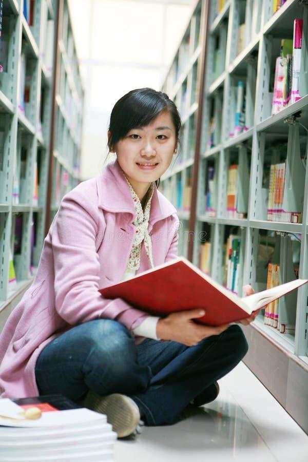 Lectura de la mujer joven en biblioteca foto de archivo libre de regalías