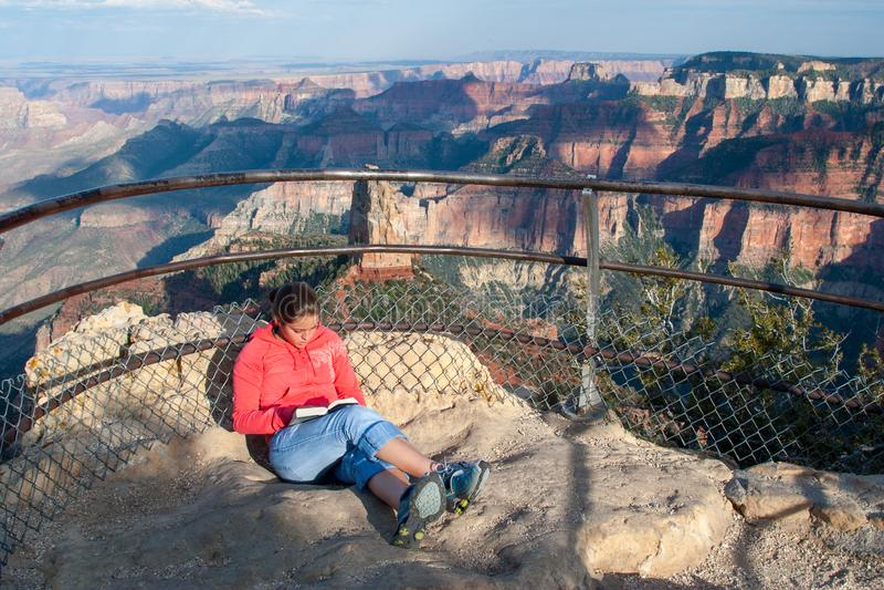 Lectura de la mujer joven en el punto imperial en el borde del norte de Grand Canyon imagen de archivo libre de regalías
