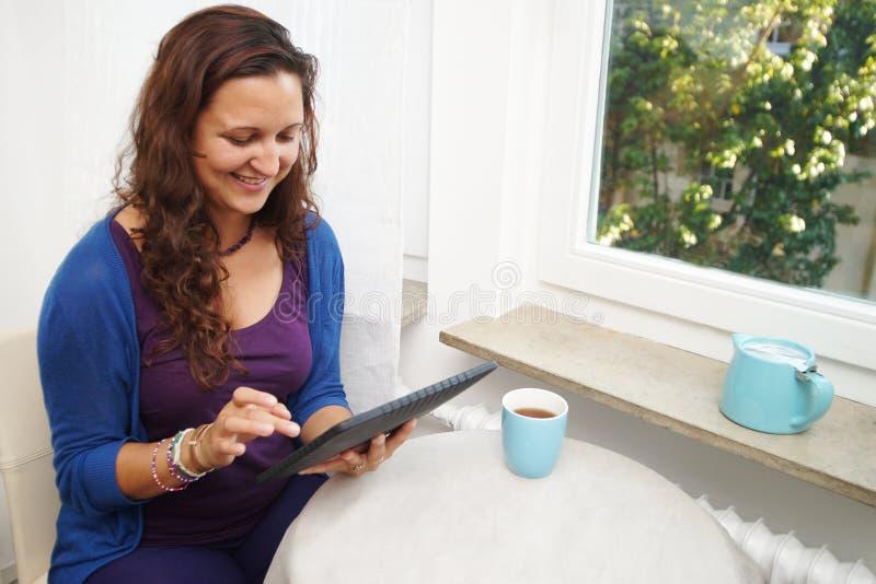 Lectura de la mujer joven en la tableta digital imágenes de archivo libres de regalías