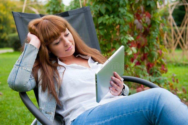 Lectura de la mujer joven en PC de la tablilla imagenes de archivo