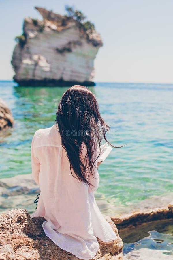 Lectura de la mujer joven en la playa blanca tropical fotos de archivo