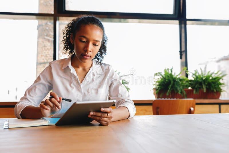 Lectura de la mujer joven de la tableta digital foto de archivo libre de regalías