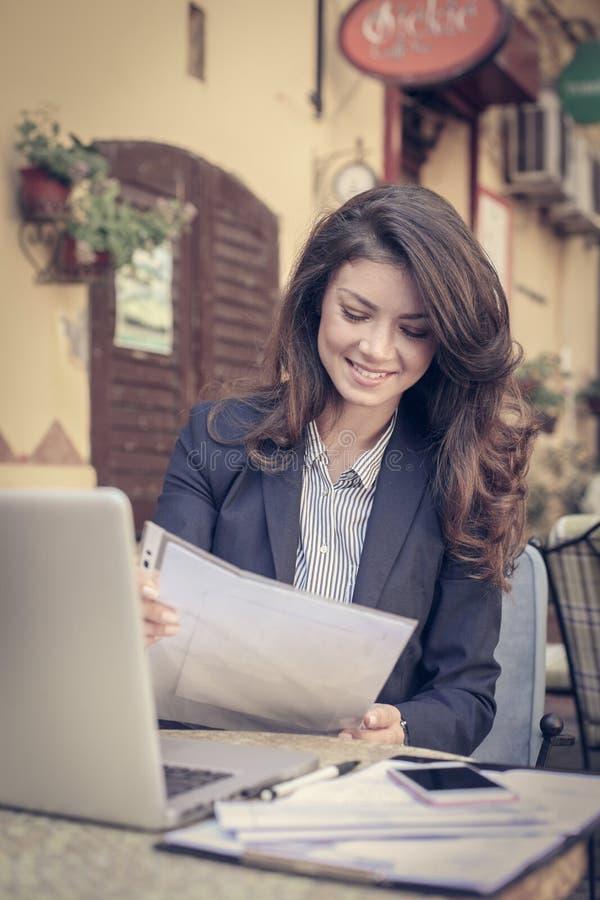 Lectura de la mujer de negocios documentos, en el café fotografía de archivo libre de regalías