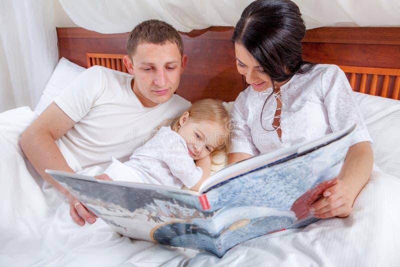 Lectura de la niña con sus padres en cama fotografía de archivo