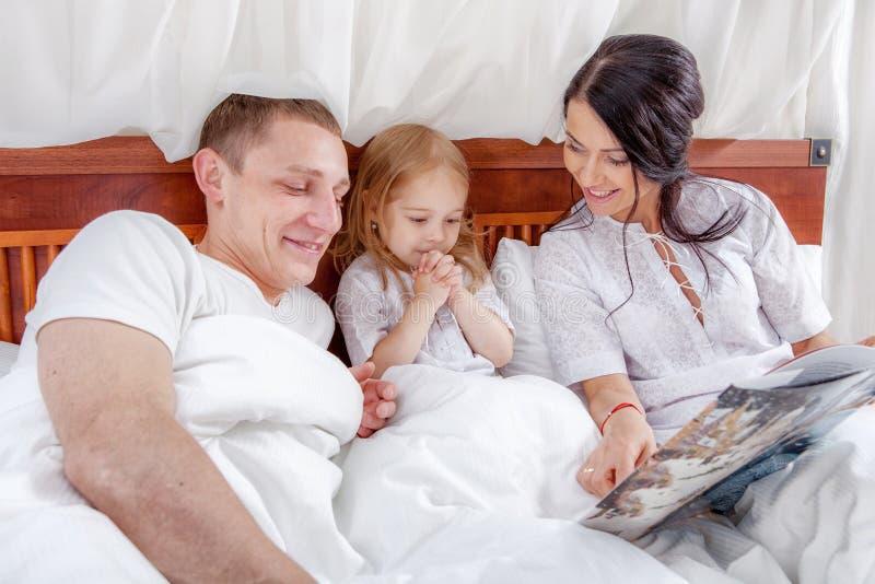 Lectura de la niña con sus padres en cama fotografía de archivo libre de regalías