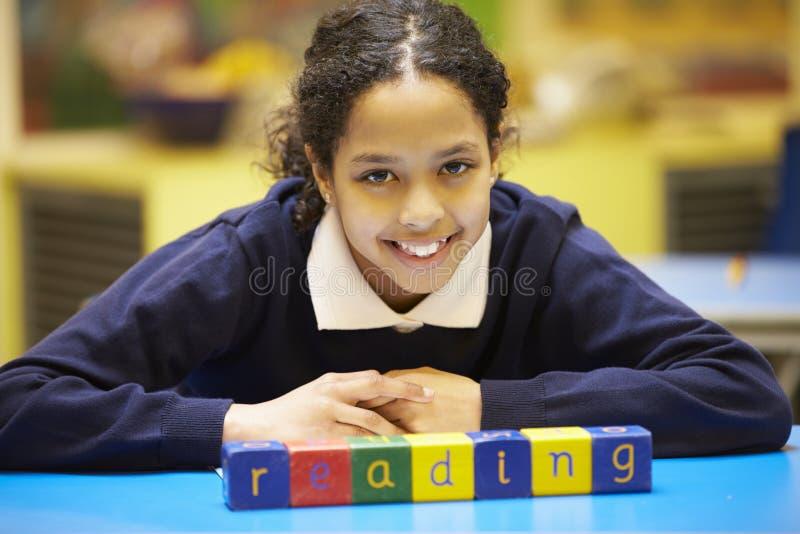 Lectura de la palabra deletreada en bloques de madera con el alumno detrás imagenes de archivo