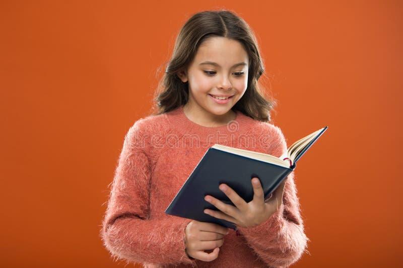Lectura de las actividades para los niños El libro del control de la muchacha leyó historia sobre fondo anaranjado El niño goza d fotografía de archivo