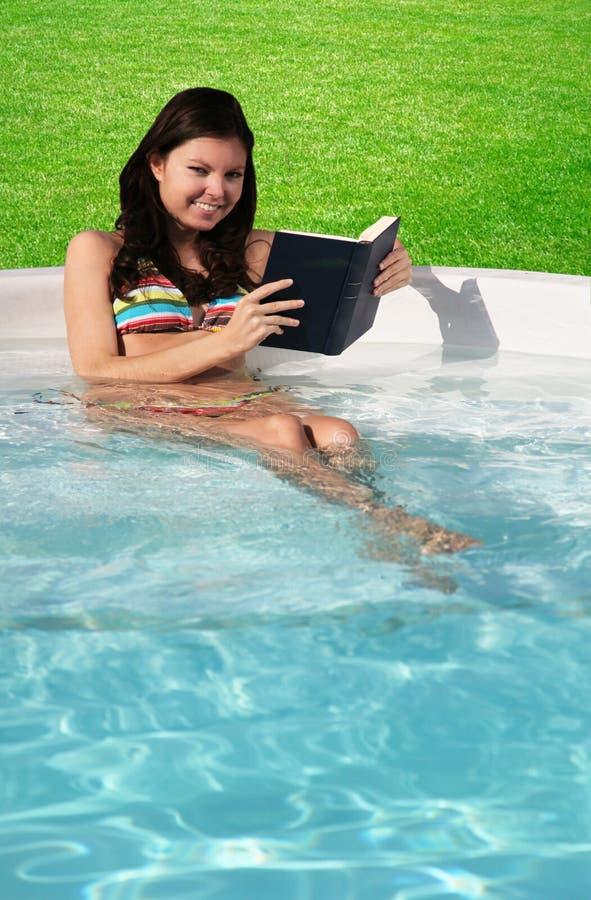 Lectura de un libro en la piscina fotos de archivo libres de regalías