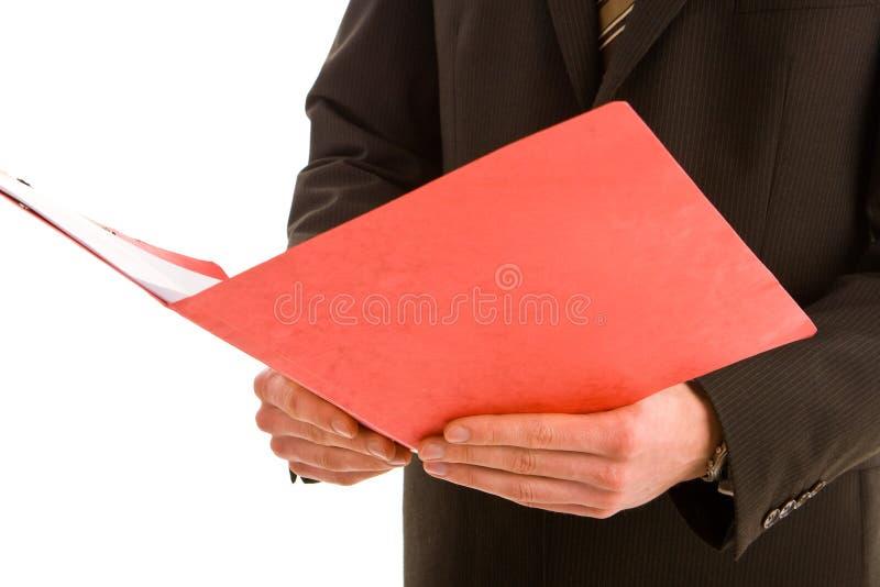 Lectura del hombre de negocios de una carpeta roja fotos de archivo