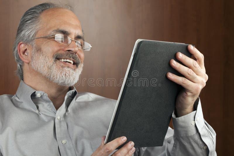 Lectura del hombre de negocios de una tablilla imagenes de archivo