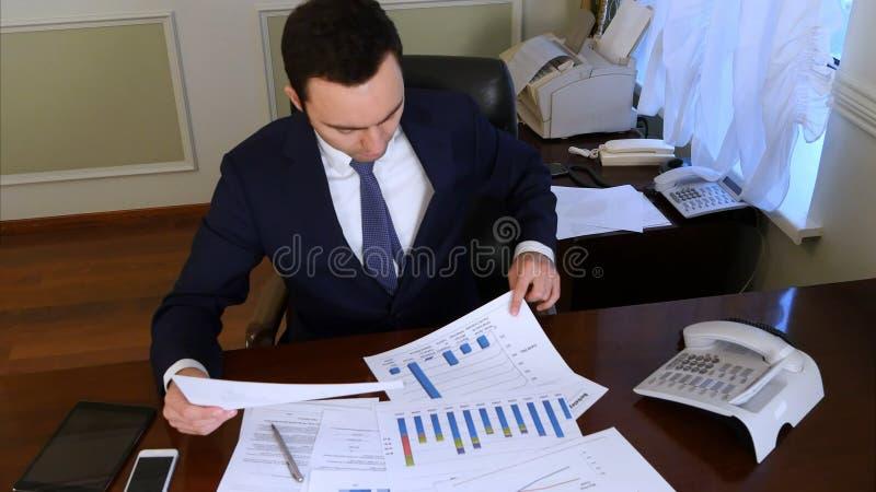 Lectura del hombre de negocios y documentos el analizar que se sientan en la oficina fotos de archivo libres de regalías