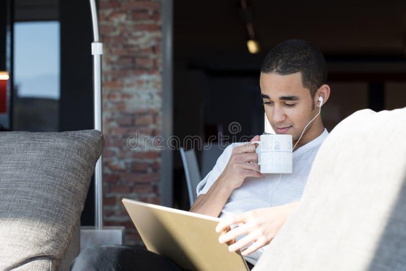 Lectura del hombre en una tableta en casa imagen de archivo