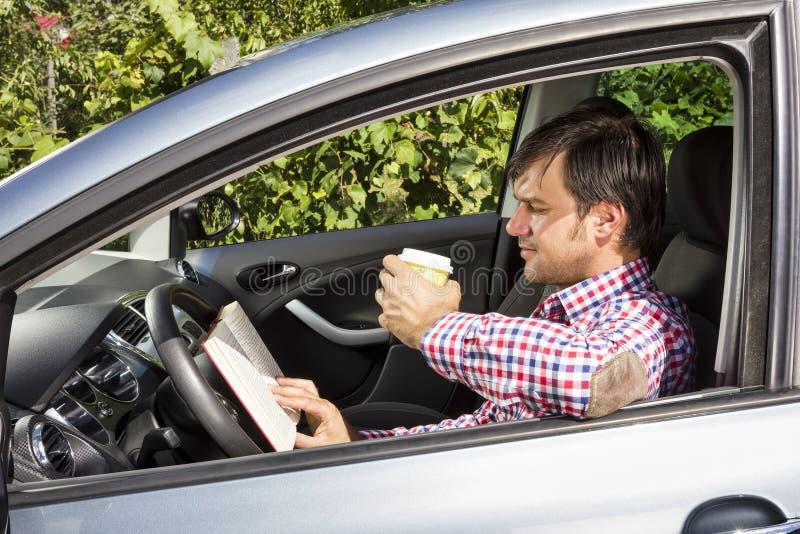 Lectura del hombre joven y café de consumición mientras que conduce imagen de archivo libre de regalías