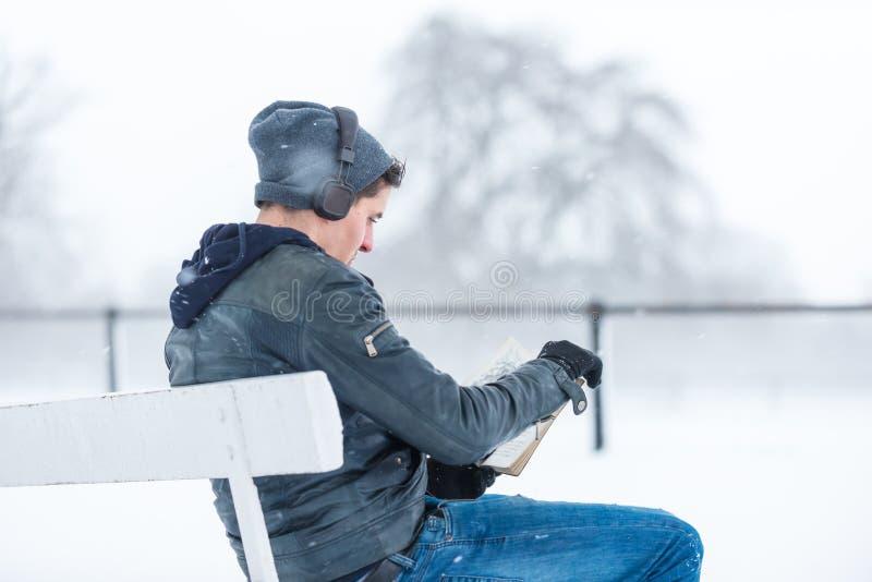 Lectura del hombre joven y música que escucha en un día nevoso fotografía de archivo libre de regalías