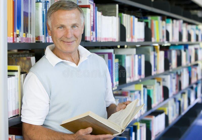Lectura del hombre mayor en una biblioteca fotos de archivo