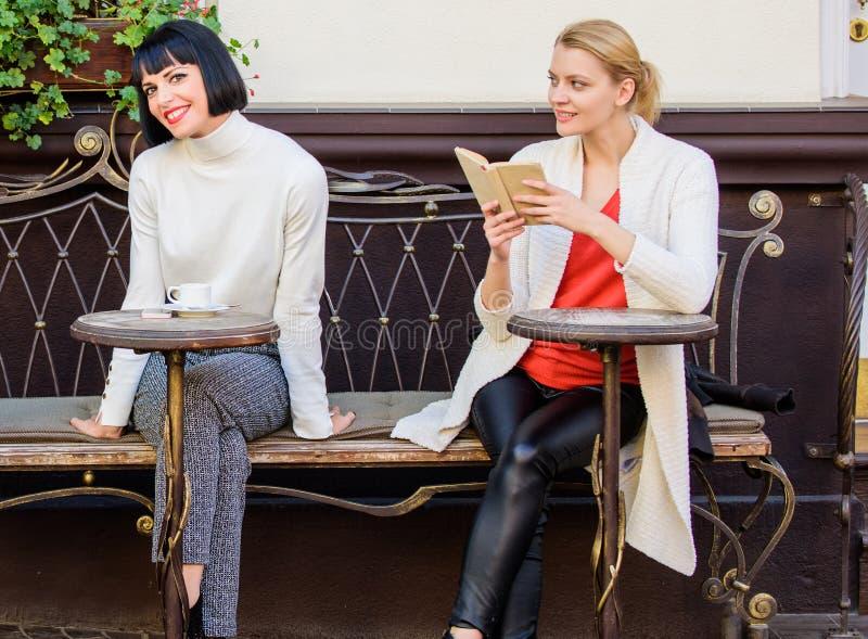 Lectura del libro inspirador Amigos de muchachas que sientan el café de consumición de la terraza del café Literatura femenina Me fotos de archivo
