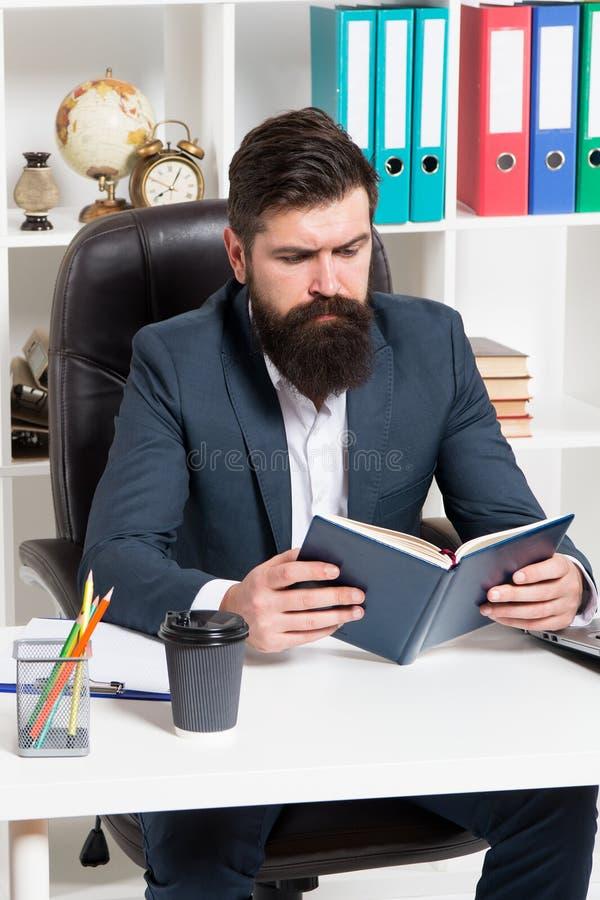 Lectura del libro del negocio de la autoridad El jefe barbudo del inconformista del hombre sienta el libro leído interior de la o fotografía de archivo