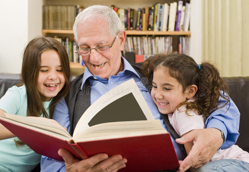 Lectura del mayor y de los niños imagen de archivo libre de regalías