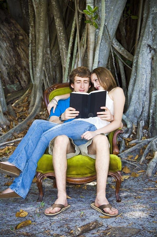 Lectura del muchacho y de la muchacha en silla fotografía de archivo libre de regalías