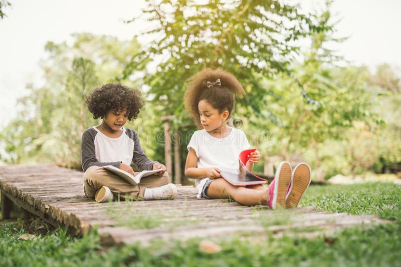 Lectura del pequeño niño con el amigo imagenes de archivo