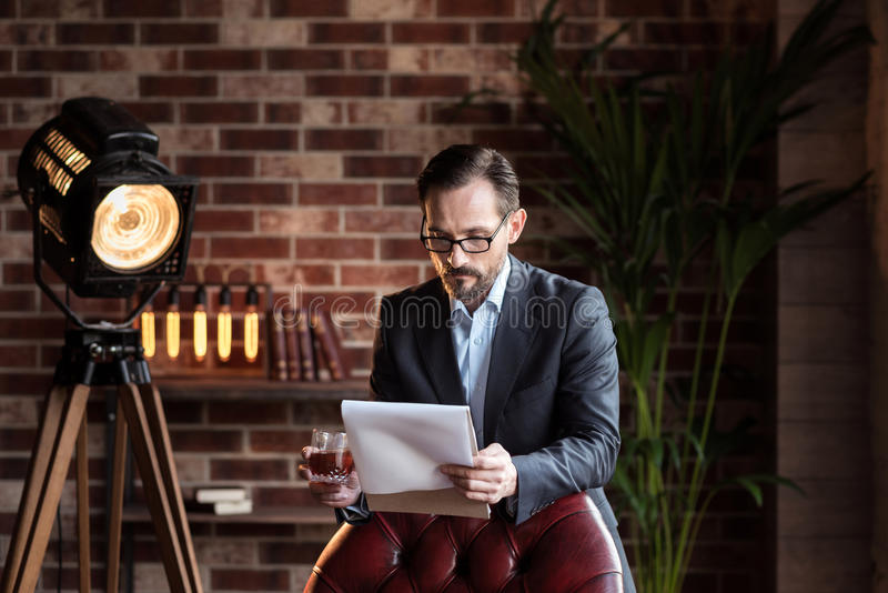 Lectura elegante seria del hombre que revisa algunos documentos imagenes de archivo