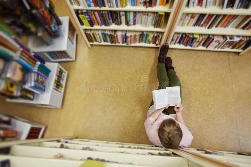 Lectura en pasillo de la biblioteca fotos de archivo libres de regalías