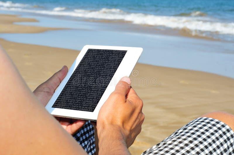 Lectura en un eBook en la playa imágenes de archivo libres de regalías