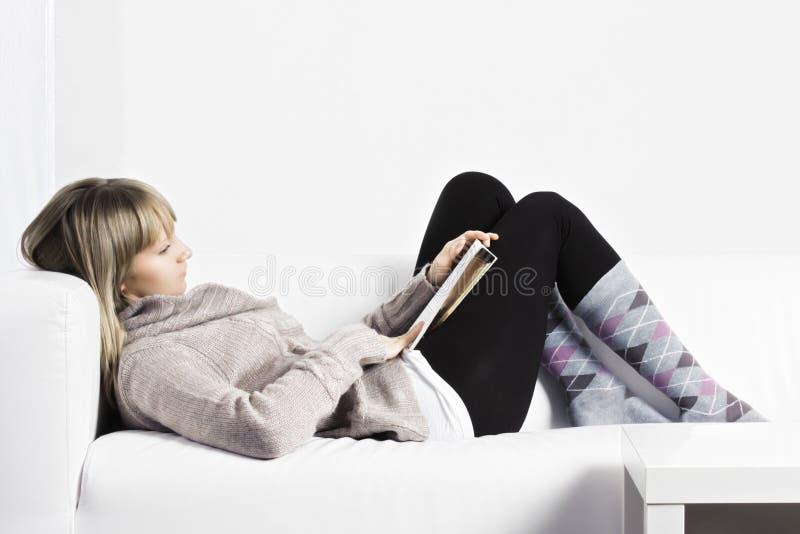 Lectura en un sofá blanco fotografía de archivo