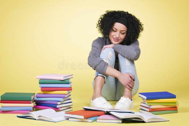 Lectura feliz de la muchacha del estudiante rodeada por los libros coloridos imagen de archivo