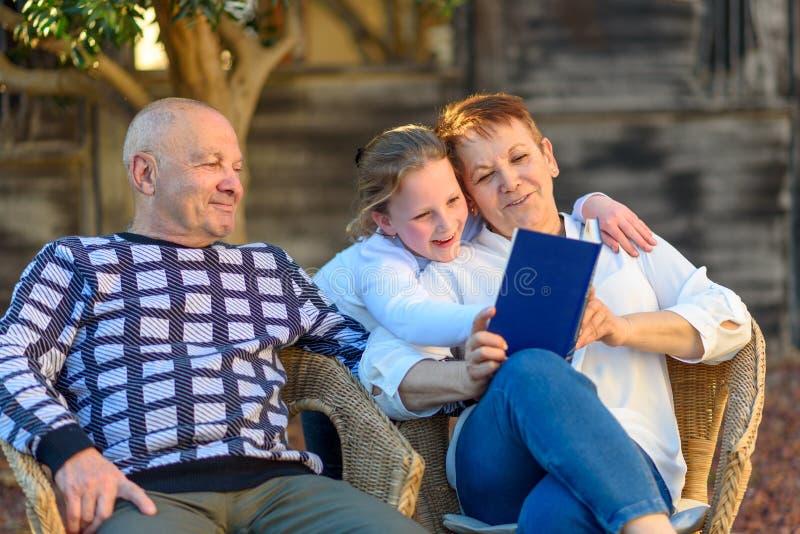 Lectura feliz hermosa del abuela y de abuelo al libro de la nieta en naturaleza en la puesta del sol fotos de archivo