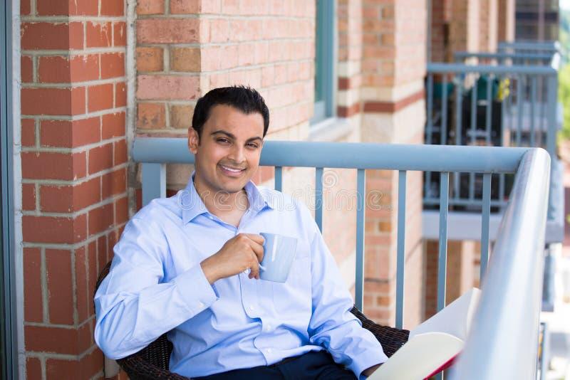 Lectura hermosa del hombre en balcón foto de archivo libre de regalías