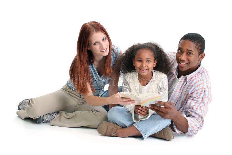 Lectura interracial de la familia junto imagenes de archivo