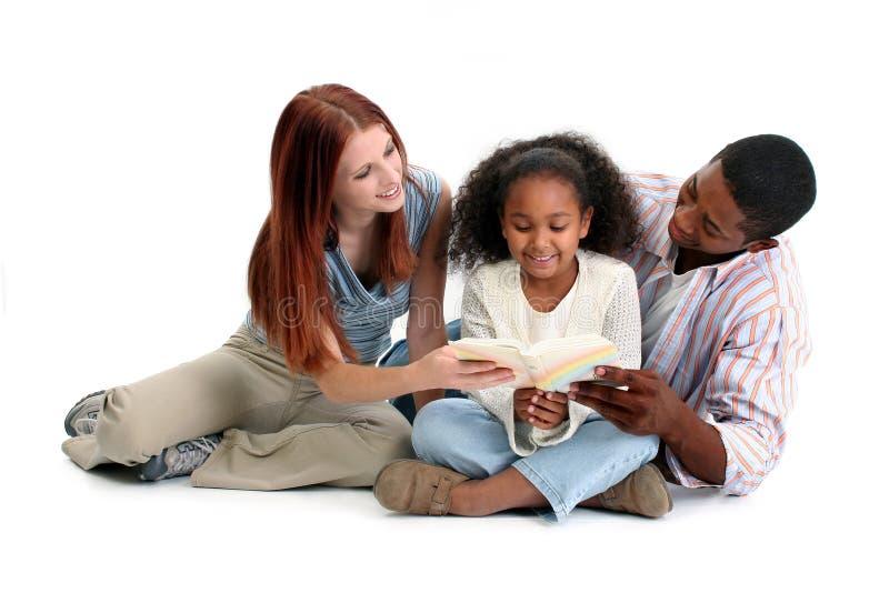 Lectura interracial de la familia junto imagen de archivo