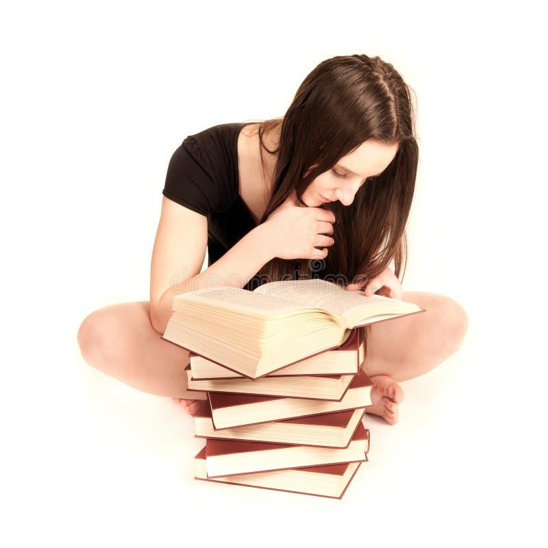 Lectura joven del estudiante en un libro foto de archivo