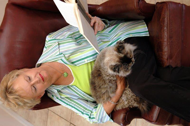Lectura mayor de la mujer con el gato fotografía de archivo libre de regalías