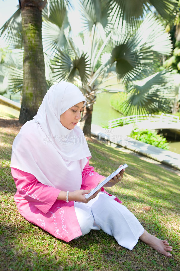 Lectura musulmán de la mujer del Malay asiático imagenes de archivo