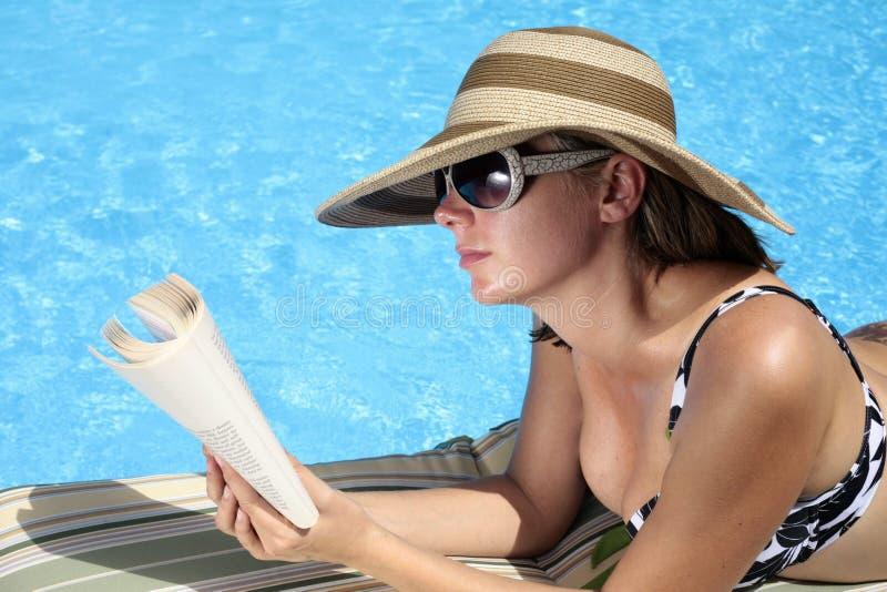 Lectura por la piscina imagen de archivo