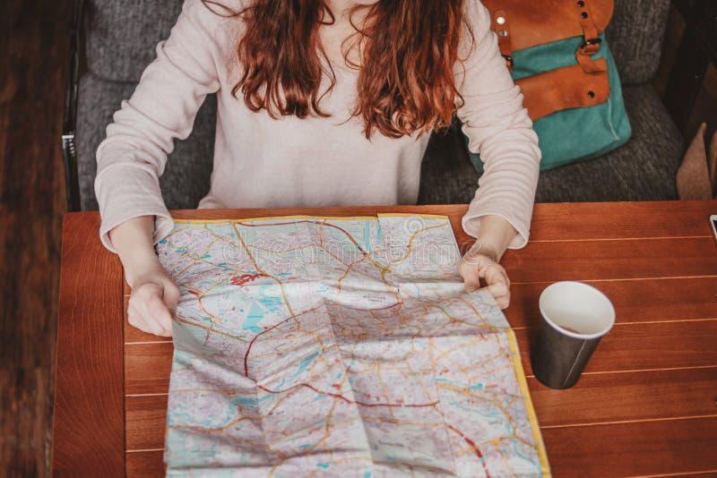 Lectura principal roja del viajero de la muchacha de la mujer joven que mira el mapa de papel en café foto de archivo