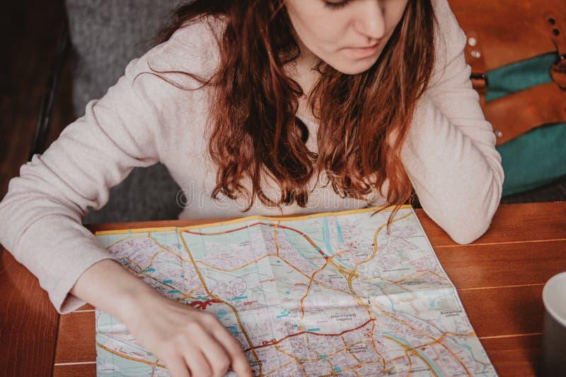 Lectura principal roja del viajero de la muchacha de la mujer joven que mira el mapa de papel en café fotos de archivo libres de regalías