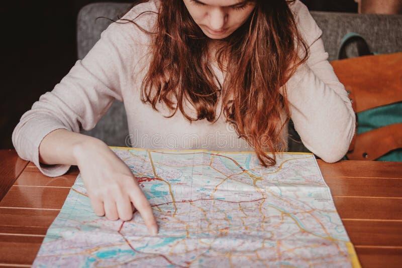 Lectura principal roja del viajero de la muchacha de la mujer joven que mira el mapa de papel en café imagen de archivo