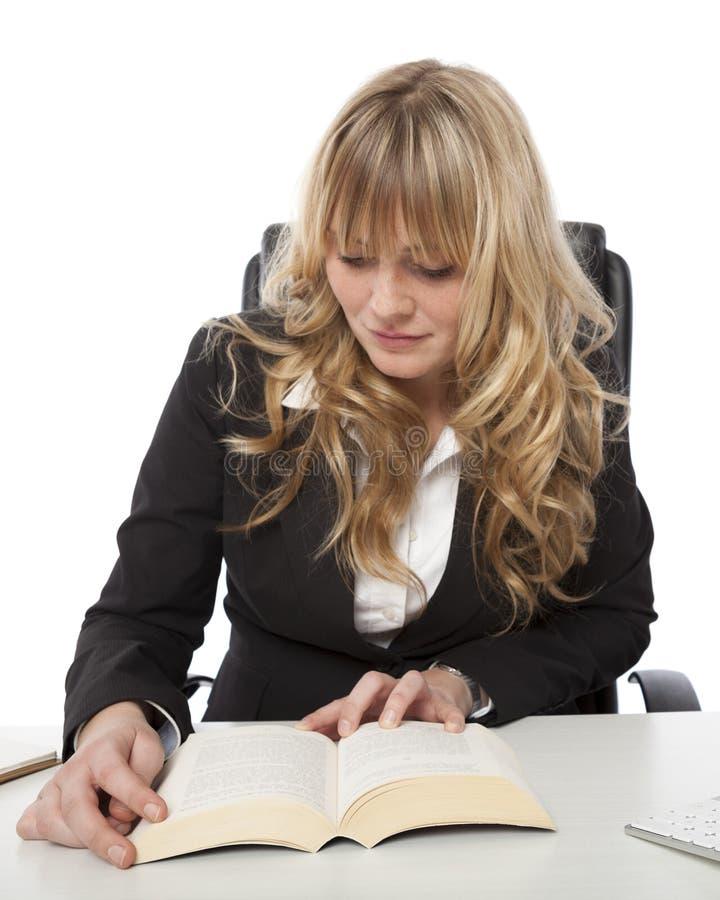 Lectura que se sienta de la empresaria joven en su escritorio foto de archivo libre de regalías