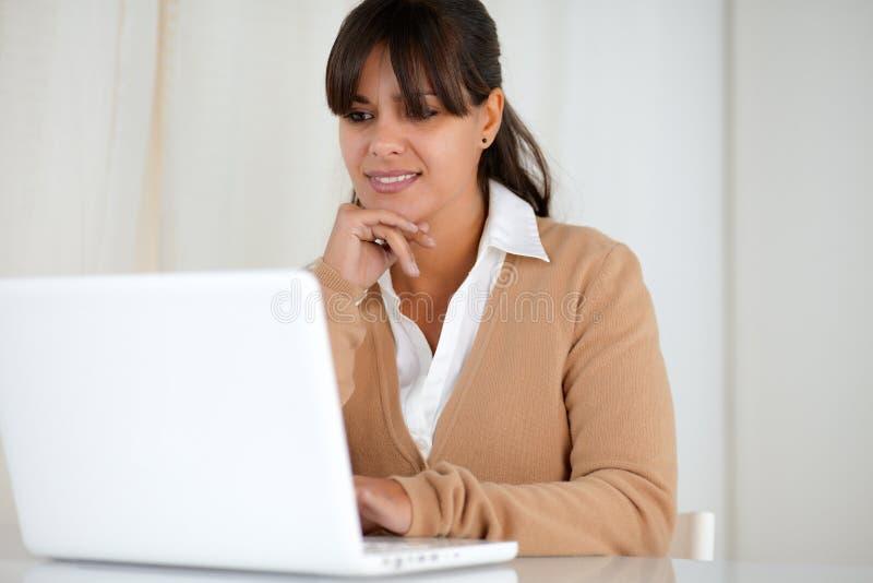 Lectura sonriente de la mujer joven en la pantalla del ordenador portátil foto de archivo