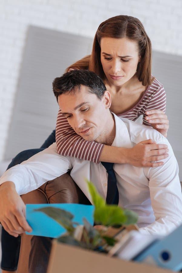 Lectura tranquila atenta del hombre mientras que su esposa cariñosa que lo abraza suavemente imágenes de archivo libres de regalías