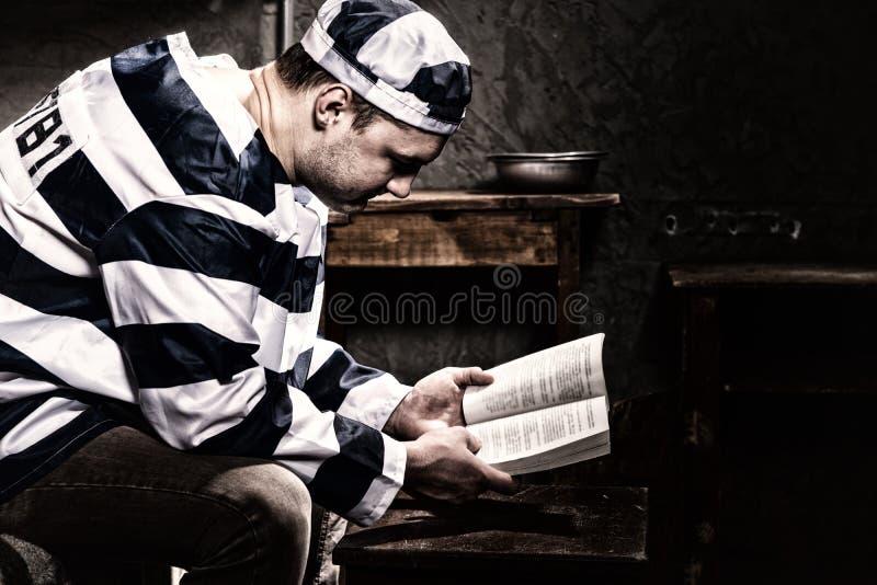 Lectura uniforme de la prisión del preso que lleva masculino un libro o una biblia w fotografía de archivo libre de regalías