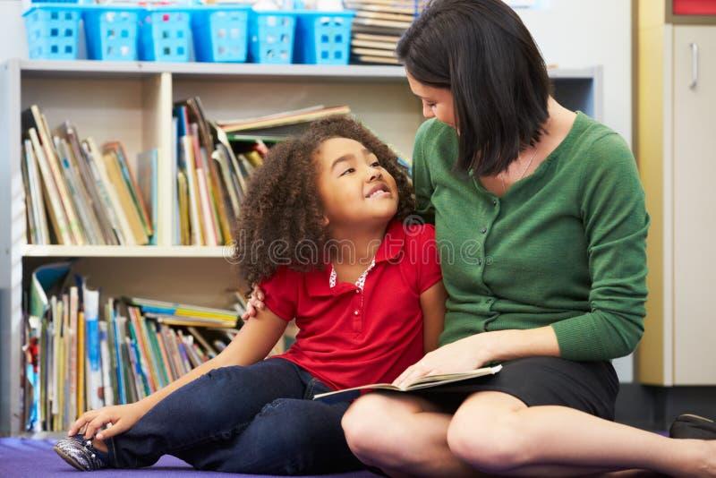 Lecture élémentaire d'élève avec le professeur In Classroom image stock