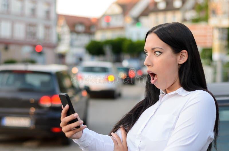 Lecture étonnée de femme sms sur son mobile images libres de droits