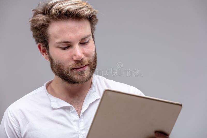 Lecture attrayante de jeune homme sur un Tablette-PC image libre de droits
